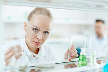 Portrait of beautiful blond woman looking at camera while performing bio experiment in laboratory