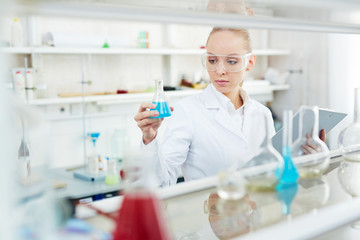 Portrait of beautiful female chemist working on research in modern laboratory holding test tubes with colored liquid