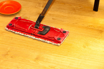 Red mop cleaning wooden floor
