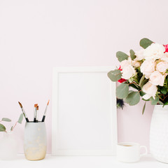 Home office desk with photo frame mock up, beautiful roses and eucalyptus bouquet in front of pale pastel pink background. Blog, website or social media concept .