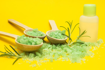 Green herbal salt, rosemary and bottle of essential oil on a yellow background.