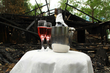 A bottle of champagne in a pail of ice, two glasses. Everything stands on a white tablecloth, and in the background - the remains of a burnt house.