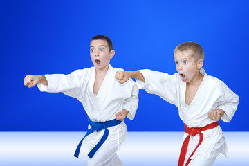 Sport children are training blows arm on a light blue background