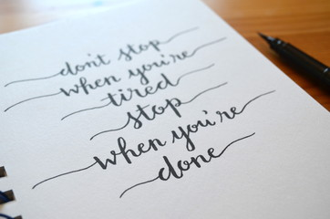 DON'T STOP WHEN YOU'RE TIRED STOP WHEN YOU'RE DONE hand lettered in notepad