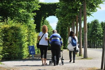 Seniorin geht mit Betreuerin und Gehhilfe im Park spazieren