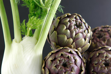 fennel and four artichokes on dark background