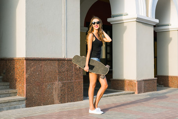Beautiful young woman in sunglasses with skate, street fashion lifestyle.