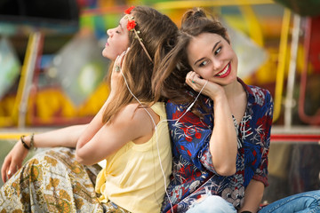 Two happy teenage girlfriends are listening to music on headphones while waiting for music concert to start