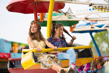 Two teenage girls are enjoying their ride at the amusement park