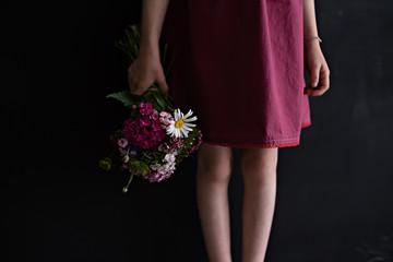 Mädchen mit Blumenkorb vor schwarzer Wand