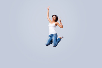Go crazy! Happy young brunette latin girl is jumping and fooling around. She is in casual outfit, showing v sign, isolated on a pure light background