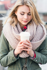 Young  girl with cup of coffee on street