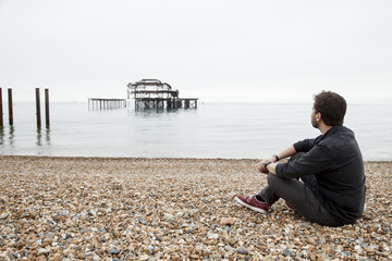 Young man sitting in a stone beach looking an old pier structure in the sea