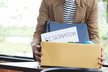 Businesswoman resignation packing up all her personal belongings and files into a brown cardboard box.