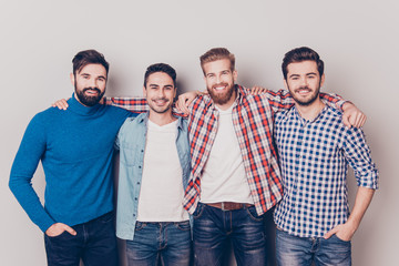 Diversity of men. Four cheerful young guys are standing and embracing, smiling, on pure background in casual outfit and jeans