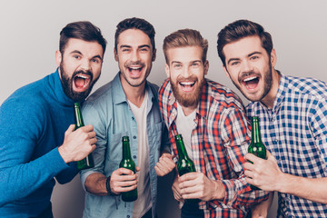 Men`s club. Four crazy friends guys are screaming with bottles in hands, all in casual shirts, isolated on grey background. They are fans of sports games as football, basketball, hockey, baseball