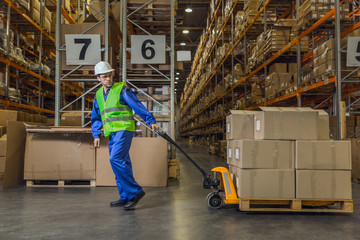 Warehouse worker dragging a cart with merchandise