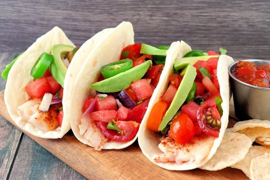 Group of spicy fish tacos with watermelon salsa and avocados close up side view