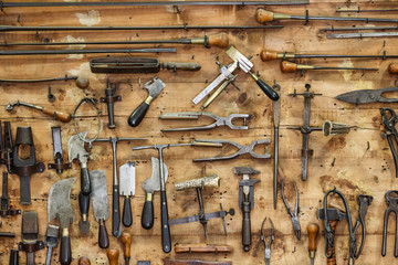 The tools of a tanner for working with leather hanging on the wall in a tannery.