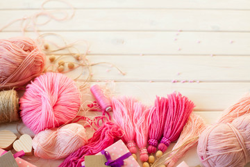 Pink tassels. Background of white wood. Women's handicrafts. The concept of creativity.