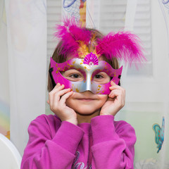 Young female child with red Mardi Gras mask