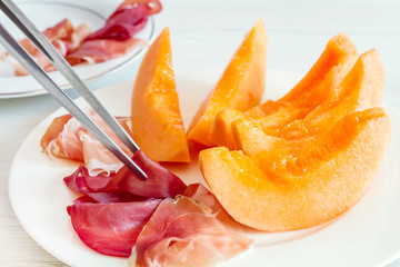 chef preparing dish with melon and ham