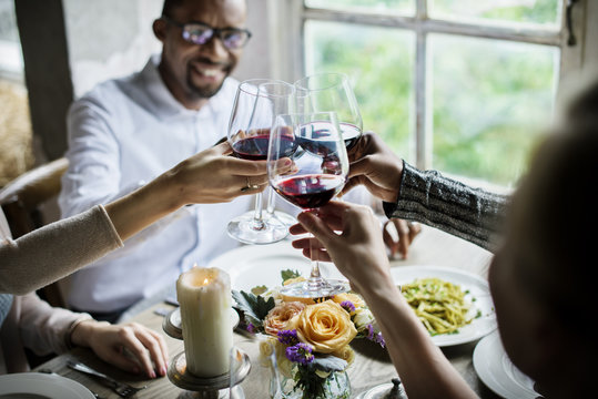 Friends toasting with red wine at restaurant table