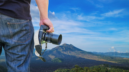 Close-up shot of man holding camera standing on the hill
