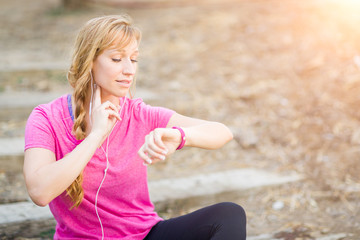 Young Fit Adult Woman Outdoors in Workout Clothes Listening To Music with Earphones Checking Her Heart Rate.