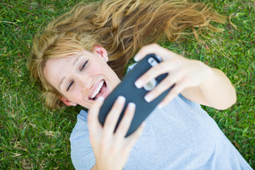 Young Adult Woman Laying in Grass Taking a Selfie with Her Smart Phone.