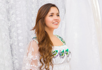 Beautiful smiling young woman wearing andean traditional clothing and posing for camera, white fabrics background