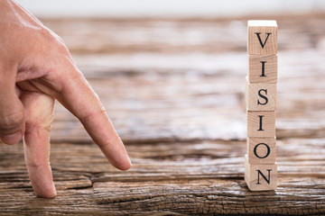 Person's Finger And Vision Word On Wooden Block