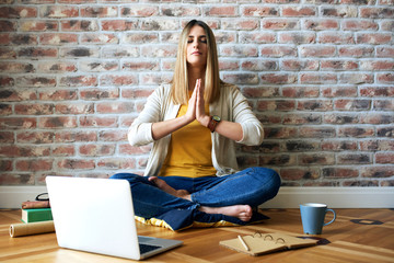 Young woman sits on the floor and meditates while working