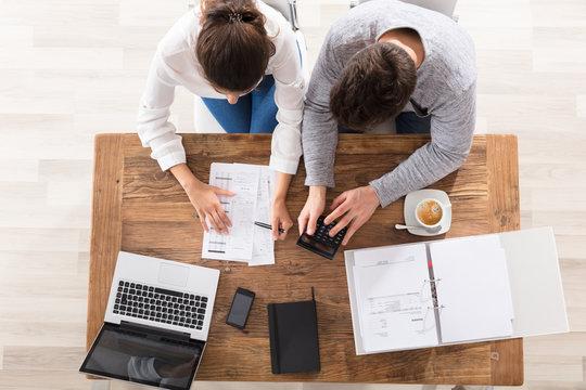 Overhead View Of Couple Calculating Bills