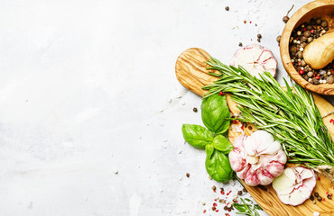 Food background, fresh rosemary, green basil, garlic, pepper on a cutting board, top view