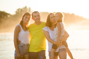 Family of four near the river outdoors during summertime