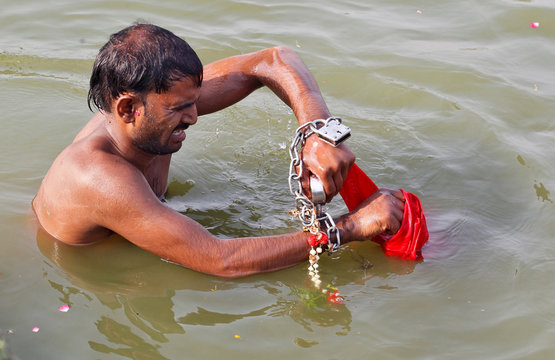 A man, whose relative says suffers from mental illness, tries to open a lock on his chained hands as he takes a dip in the waters of the Ganges river during Jyestha Purnima in Allahabad