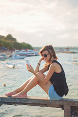 Cute girl sitting on the beach and using a cellphone.