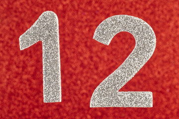 Number twelve silver color over a red background. Anniversary. Horizontal