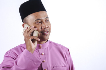 Man in traditional clothing with smartphone celebrate Eid Fitr.