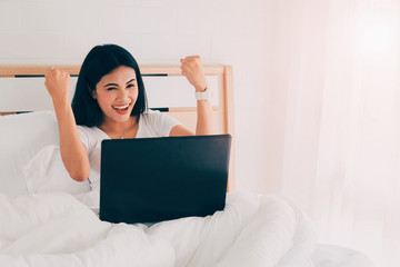 Young asian woman happy and using laptop to working in bedroom.