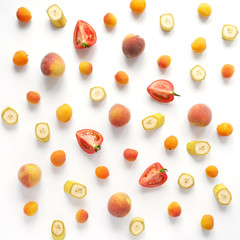 Apricots, bananas, peaches and tomatoes on a white background. Pattern of vegetables and fruits. Top view.
