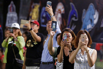 Friends and relatives take pictures of the Future League American football youth league match between the Sharklets and the Eagles in Beijing