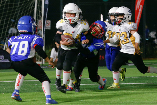 Sharklets players defend against the Eagles during their Future League American football match in Beijing