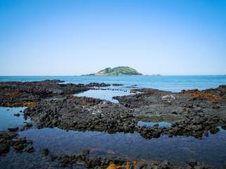 Idyllic sand beach with volcanic black rocks in Jeju Island, South Korea