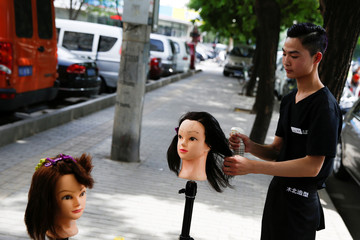 An apprentice practices hairstyling on a doll in the street outside a hair salon in Beijing