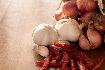 Garlic, shallots, dried chilies on wood background.