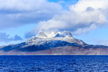 Clouds over Sermitsiaq mountain covered in snow with blue sea in the foreground, nearby Nuuk city, Greenland