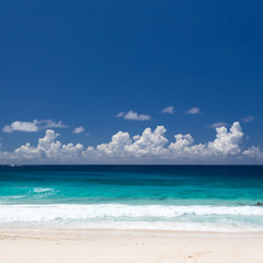 Empty tropical beach on Seychelles featuring levels of white sand, emerald water, dark blue water, and dark blue sky with white clouds. Copy space on the sky.