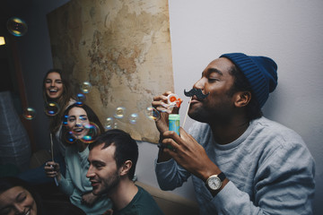 Young friends looking at man blowing bubbles against wall in dorm room